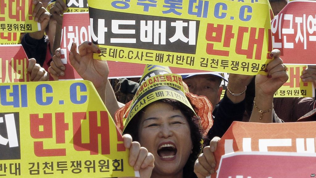 """A resident in a rural South Korean town shouts slogans to protest a plan to deploy an advanced U.S. missile defense system called Terminal High-Altitude Area Defense, or THAAD, in their neighborhood, in Seoul, South Korea, Wednesday, Oct. 5, 2016. A private golf course in South Korea's southeast has been chosen as the new site for an advanced U.S. missile defense system to be deployed by the end of next year to protect against North Korean threats, Seoul's Defense Ministry said last Friday. The letters read """"Desperately oppose, Deployment THAAD."""" (AP Photo/Ahn Young-joon)"""